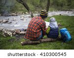 teenager sitting near a fire in ... | Shutterstock . vector #410300545