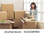 Stock photo attractive young woman is moving sitting among cardboard boxes using a laptop and smiling 410338984