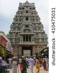 Small photo of Trichy, India - October 15, 2013: One of the shorter gopurams near inner circle of Ranganathar Temple. Facade is set with statues. Pastel colors galore. People walking to gopuram.