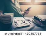 Small photo of Glasses put down on table beside notebooks and pen while young freelance worker using smart phone and holding coffee cup in morning time on work day, Working at home concept with vintage filter effect