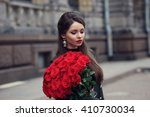 Stock photo portrait of young stylish pretty beautiful girl with big bouquet of red roses 410730034