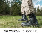 Poacher at Work Concept. Poacher Military Grade Shoes Closeup with Forest in the Background. - stock photo