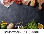 Small photo of Ciabatta sandwich cooking with romaine salad, prosciutto and mozzarella cheese over stone background. Top view with copy space