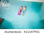 High angle view of couple relaxing on inflatable raft at swimming pool - stock photo