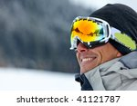 skier smiling and wearing ski glasses in the mountains - stock photo