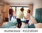 Stock photo family on vacation with children playing on hotel bed 411218164