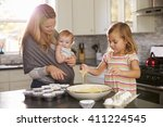 young girl preparing cake mix... | Shutterstock . vector #411224545