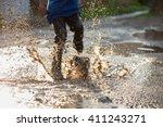 little boy splashing in a mud... | Shutterstock . vector #411243271