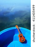 Small photo of Ukulele lay on blue boat floating on water, relax with instrumental Ukulele