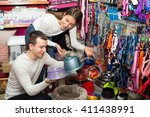 Stock photo young boyfriend helping girl to choose bowl in pet store focus on guy 411438991