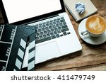 Stock photo office stuff with movie clapper laptop and coffee cup pen notepad on the wood table top view shot 411479749