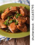 Small photo of Adobo Chicken with herbs close-up on a plate on the table. Vertical