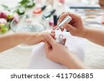 Small photo of Manicurist applying transparent base coat to nail