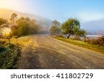road through the valley near the forest in foggy mountains at hot sunrise - stock photo