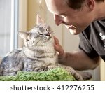 Stock photo cat and man portrait of happy cat with close eyes and young man people playing with the kitten 412276255
