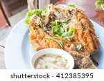 Small photo of Fried snapper with chili sauce on the plate.