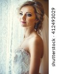 beautiful bride by the window | Shutterstock . vector #412493029