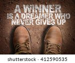 Small photo of Top View of Boot on the trail with the text: A Winner is a Dreamer Who Never Gives Up