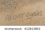 "Small photo of written words ""All over again"" on sand of beach"