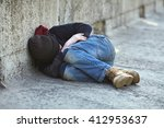 Small photo of young homeless boy sleeping on the bridge, poverty, city, street