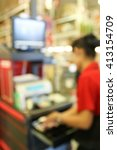 Small photo of abstract blurred cashier at supermarket checkout in department store.