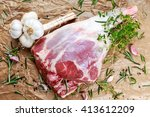 Small photo of Raw lamb leg on crumpled paper background with herbs.