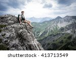 hiker sits on a mountain cliff...   Shutterstock . vector #413713549