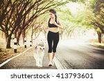 Stock photo sport girl is running with a dog siberian husky at the morning on the road 413793601