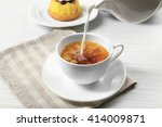 milk poured into a cup of tea ... | Shutterstock . vector #414009871