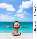 Small photo of Happy freedom carefree bikini woman enjoying summer beach vacation with arms up cheering in success. Girl feeling free with sun hat relaxing sunbathing on holidays. Caribbean south tropical travel.