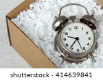 Small photo of wind-up alarm clock in the parcel. Delivery concept