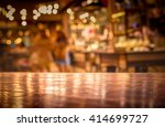 Stock photo real wood table with light reflection on scene at restaurant pub or bar at night blurred 414699727