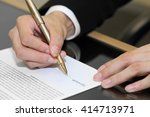 Small photo of close-up on a businessman hand signing a contract paper