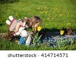 little girl smelling flower in... | Shutterstock . vector #414714571