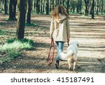 Stock photo girl walking dog in park 415187491