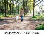 Stock photo girl walking dog in park 415187539