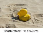 Small photo of Summer yellow duck beach toy affix in the dry sand in Valencia, Spain. Selective focus.