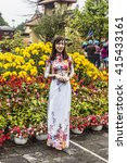 Small photo of HUE, VIETNAM - FEBRUARY 28, 2016: A woman is posing for a fotgraph wearing an Ao Dai. The Ao Dai is the national dress in Vietnam.