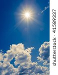 bright sun on blue sky with fluffy clouds - stock photo