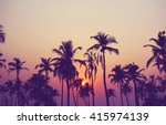 Stock photo silhouette of palm trees at sunset vintage filter 415974139
