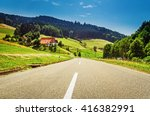 Driving along a country road in summer mountain valley in Germany, Black Forest. Scenic countryside landscape with an old traditional house. - stock photo