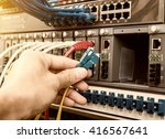 Small photo of hand of administrator holding optic fiber cables with connectors
