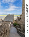 Small photo of MONT-SAINT-MICHEL, FRANCE - JUL 15, 2015: Fortress wall and adjoined to her building. In the background at low tide exposing the seabed