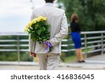 Young Man Hides A Bouquet Of...