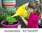 Young Girl Watering Basil Plan...