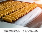 Small photo of Eclair shells on conveyor line. Rows of eclair shells. Huge order for confectionery plant. Standard size and shape.