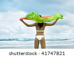 Girl gazing towards the sea on beach with shawl flying in the wind, enjoying the clean minimal environment and fresh sea salt air.  Gold Coast Beach, Queensland, Australia. - stock photo