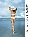 Girl in white bikini walking in the water at the beach holding on to her white sun hat. Gold Coast Beach, Queensland, Australia. - stock photo
