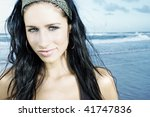 Australian girl on the beach. head shot pretty brunette with head band looking into camera. bright and sunny. slight smile and beautiful eyes. - stock photo