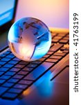 glass globe on a laptop keyboard - stock photo